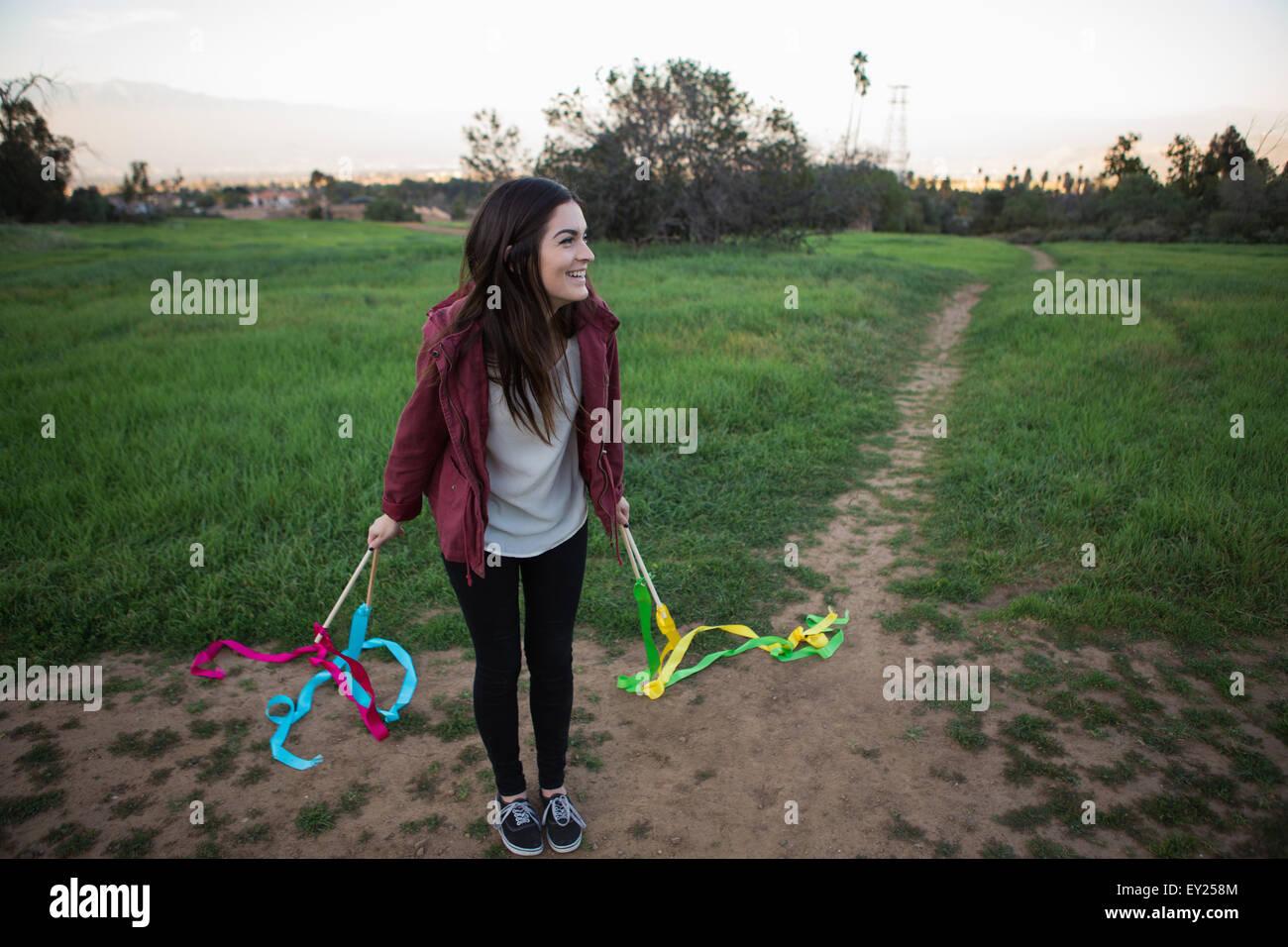 Mujer joven de pie en el campo de la celebración de la danza cintas Imagen De Stock
