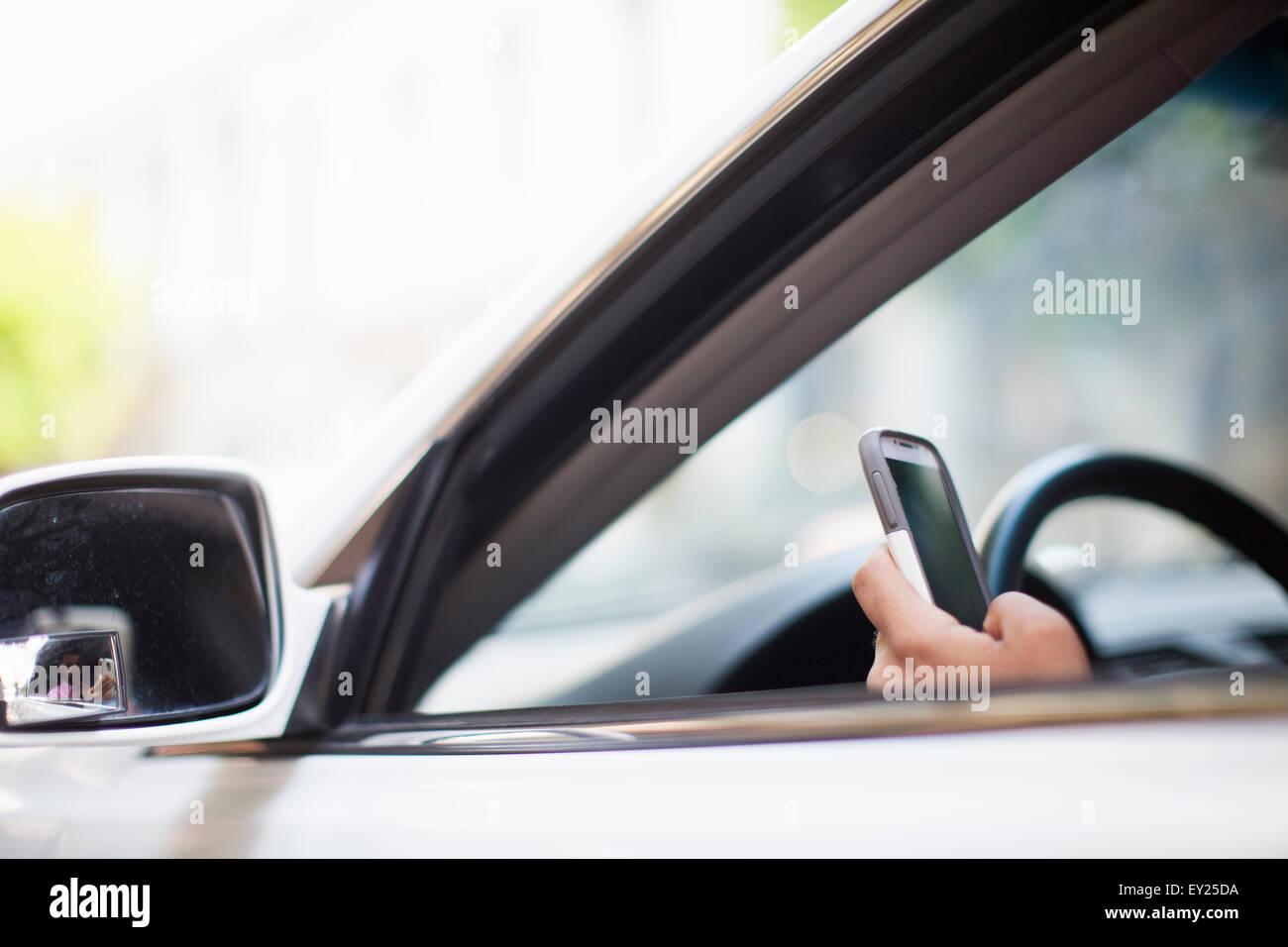 La mano del empresario mediante smartphone a car window Foto de stock