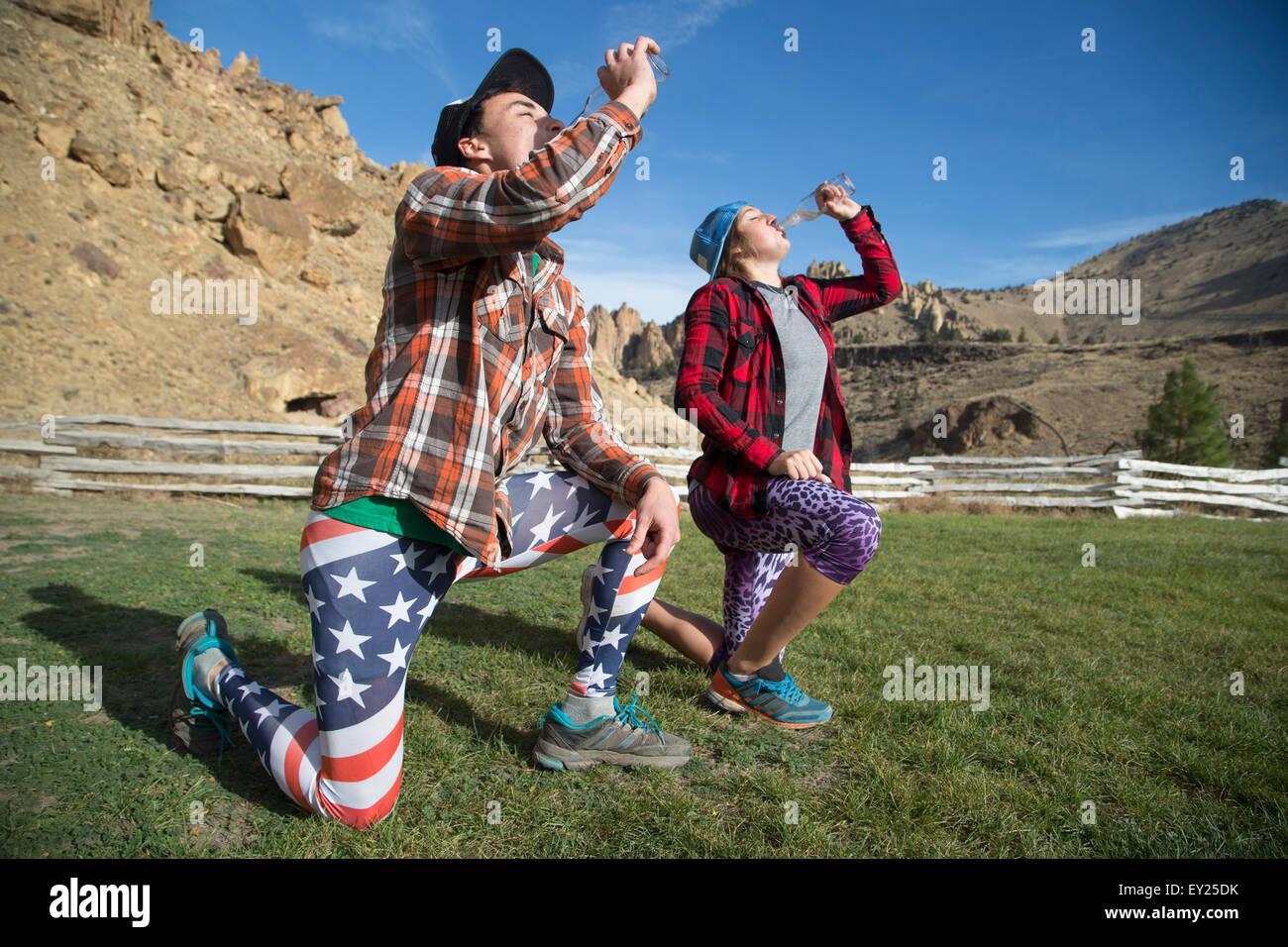 Amigos arrodillado y beber, Smith Rock State Park, Oregón, EE.UU. Imagen De Stock