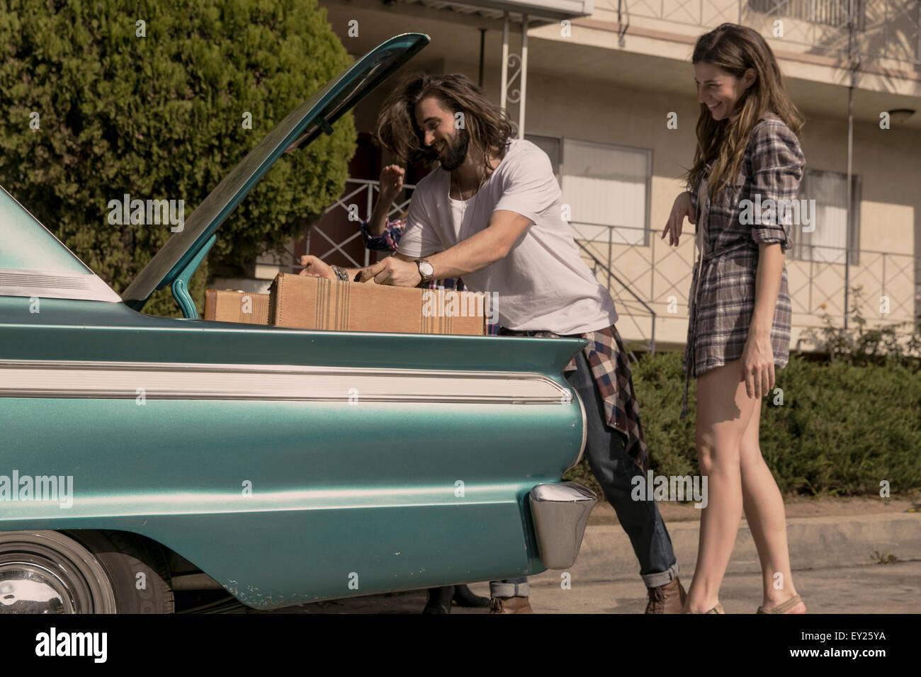 Pareja joven packing vintage car boot para Road Trip. Imagen De Stock