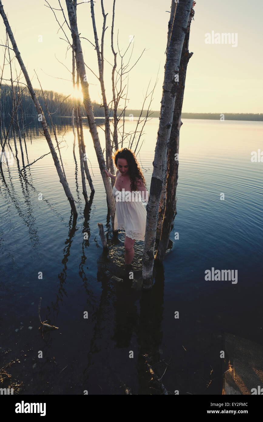 Una mujer en un vestido blanco camisón o en aguas poco profundas en el crepúsculo Foto de stock