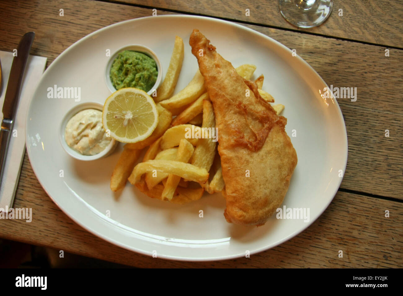 Fish & Chips inglés tradicional con puré de guisantes y salsa tártara. Imagen De Stock
