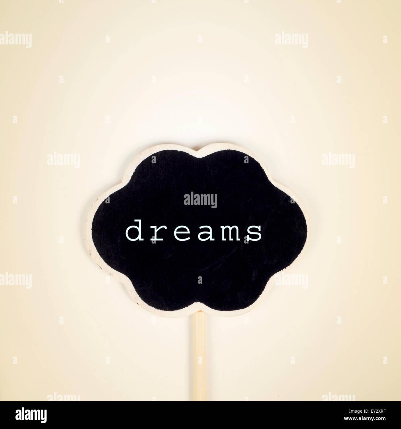 Blackboard en la forma de un pensamiento de burbuja con el texto escrito en sueños sobre un fondo de color beige, Foto de stock