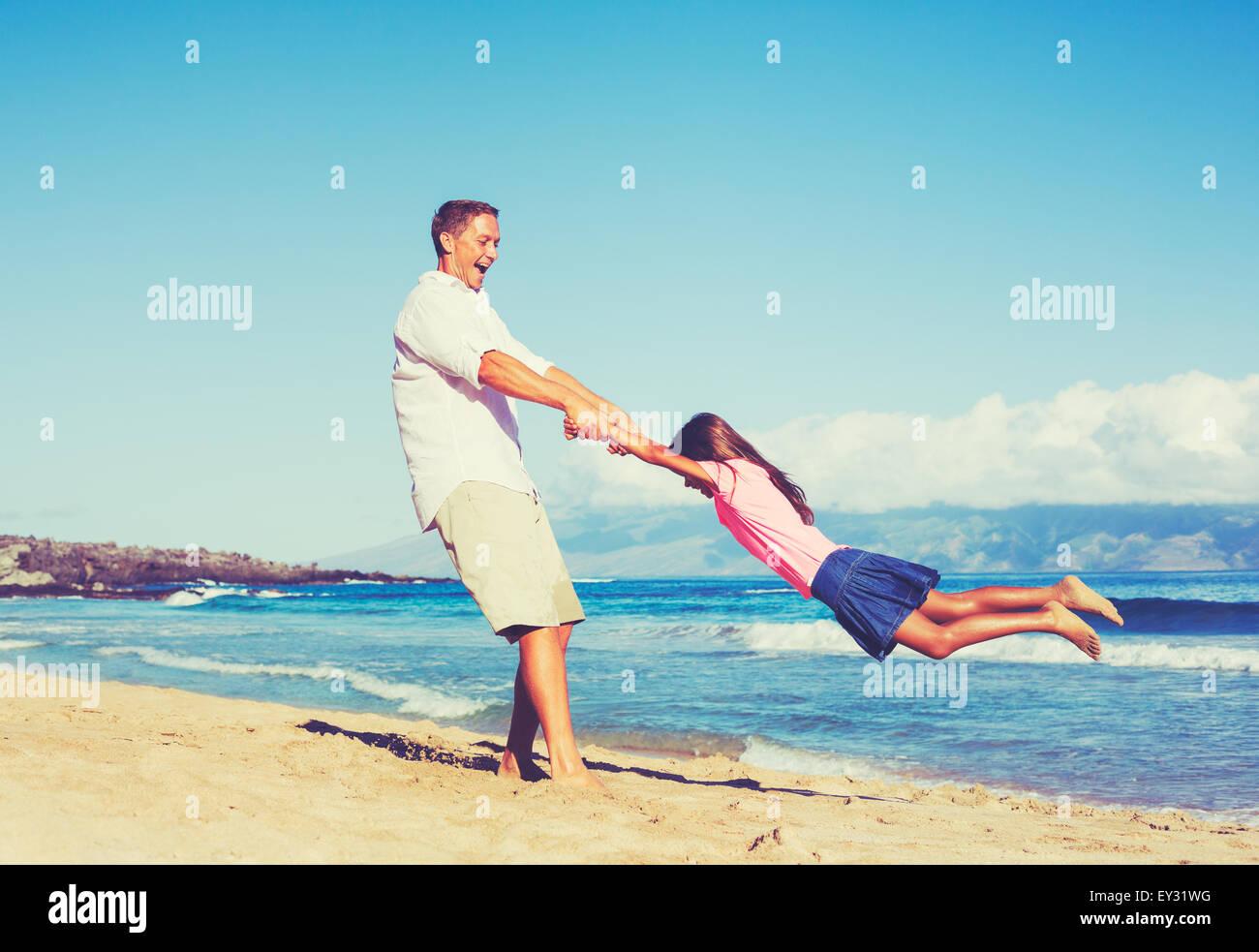 Padre e hija feliz jugando juntos en la playa. Divertidas vacaciones verano de estilo de vida. Imagen De Stock