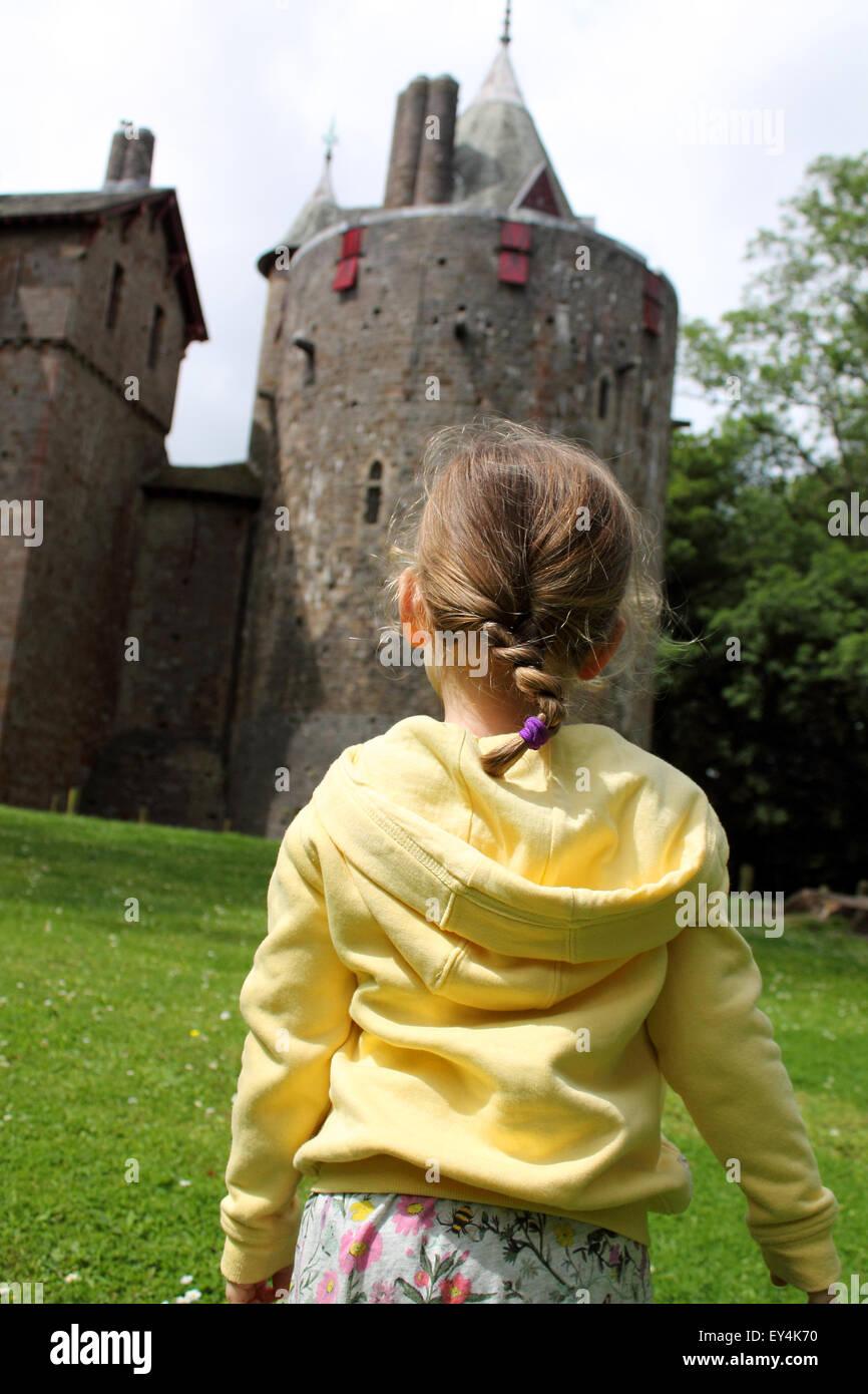 Niña mirando hacia arriba a un castillo o Castell Coch, Cardiff, Gales del Sur, Reino Unido Foto de stock