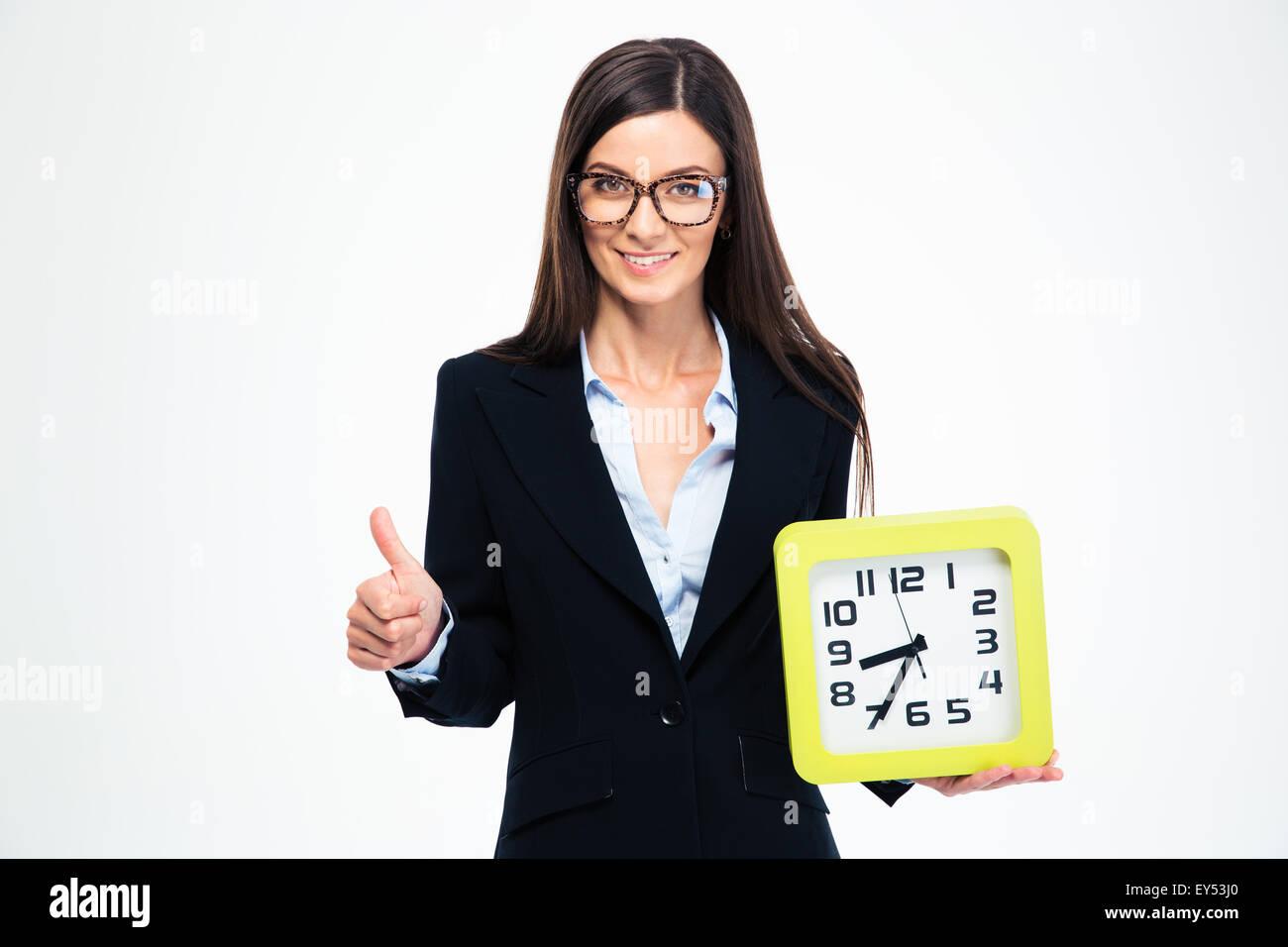 La empresaria sonriente sosteniendo el reloj y mostrando pulgar arriba aislado sobre un fondo blanco. Imagen De Stock