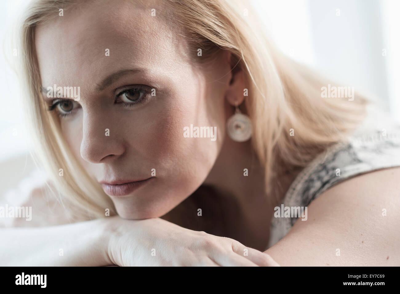 Pensativo mediados de-mujer adulta tumbado en la cama Imagen De Stock