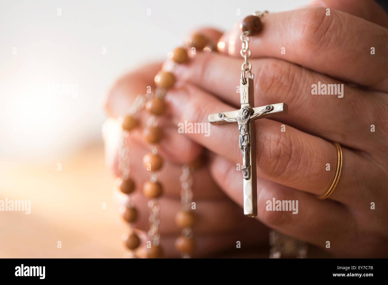 Mujer orando con el rosario entre las manos Imagen De Stock
