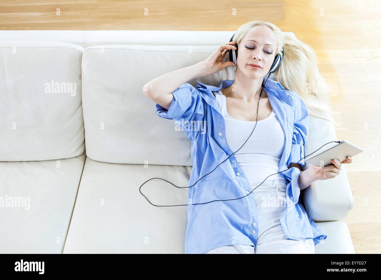 Mujer rubia, escuchar música con auriculares Imagen De Stock