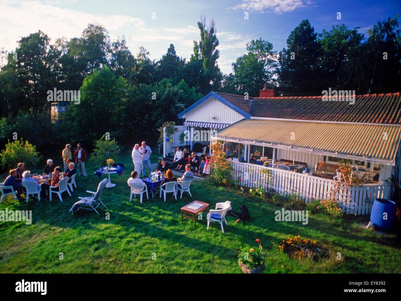 Amigos compartiendo la comida, el café y la conversación en casa de verano en la isla Tranholmen en Estocolmo Imagen De Stock