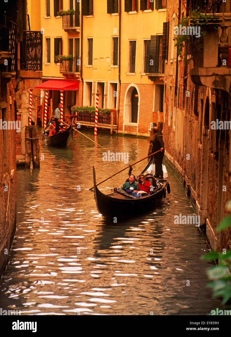 Las góndolas repletas de turistas pasando por estrechos canales en Venecia. Imagen De Stock