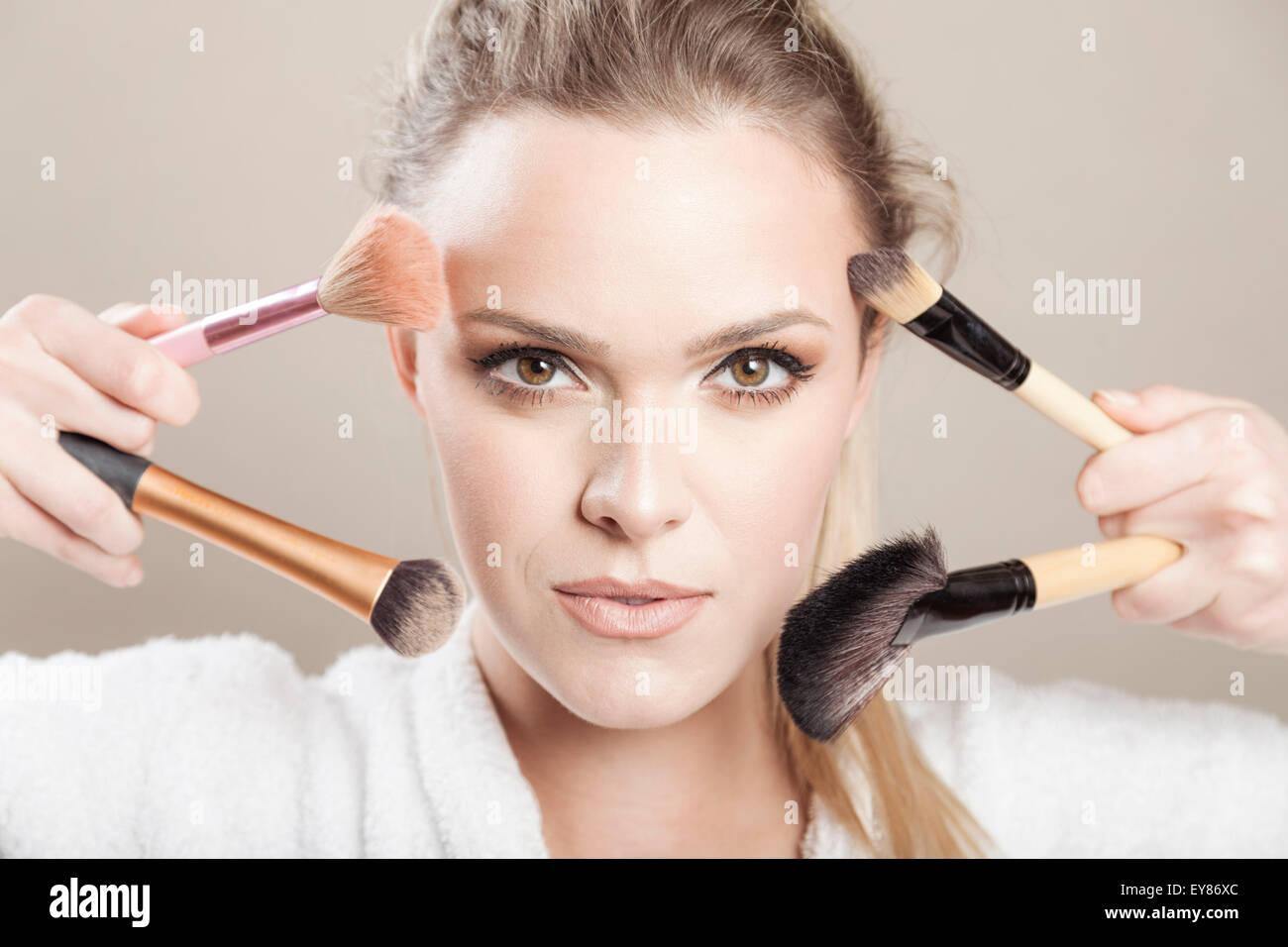 Mujer joven sujetando brochas de maquillaje Imagen De Stock