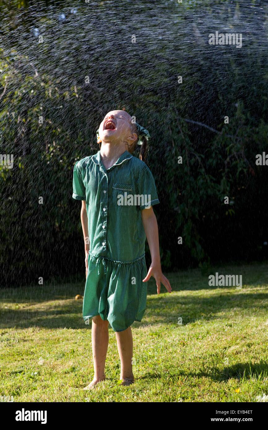 Chica en vestido verde jugando bajo un rociador de agua. Foto de stock