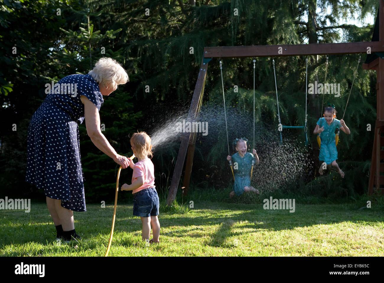 Familia jugando en el jardín con una manguera de agua en verano. Imagen De Stock