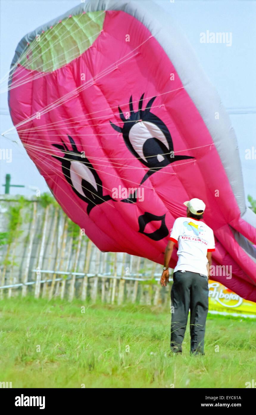 Hombre delante de la cometa humana (más ligera que al aire, con todo el globo de gatitos) durante el Festival Internacional de Kite de Yakarta 2004. Foto de stock