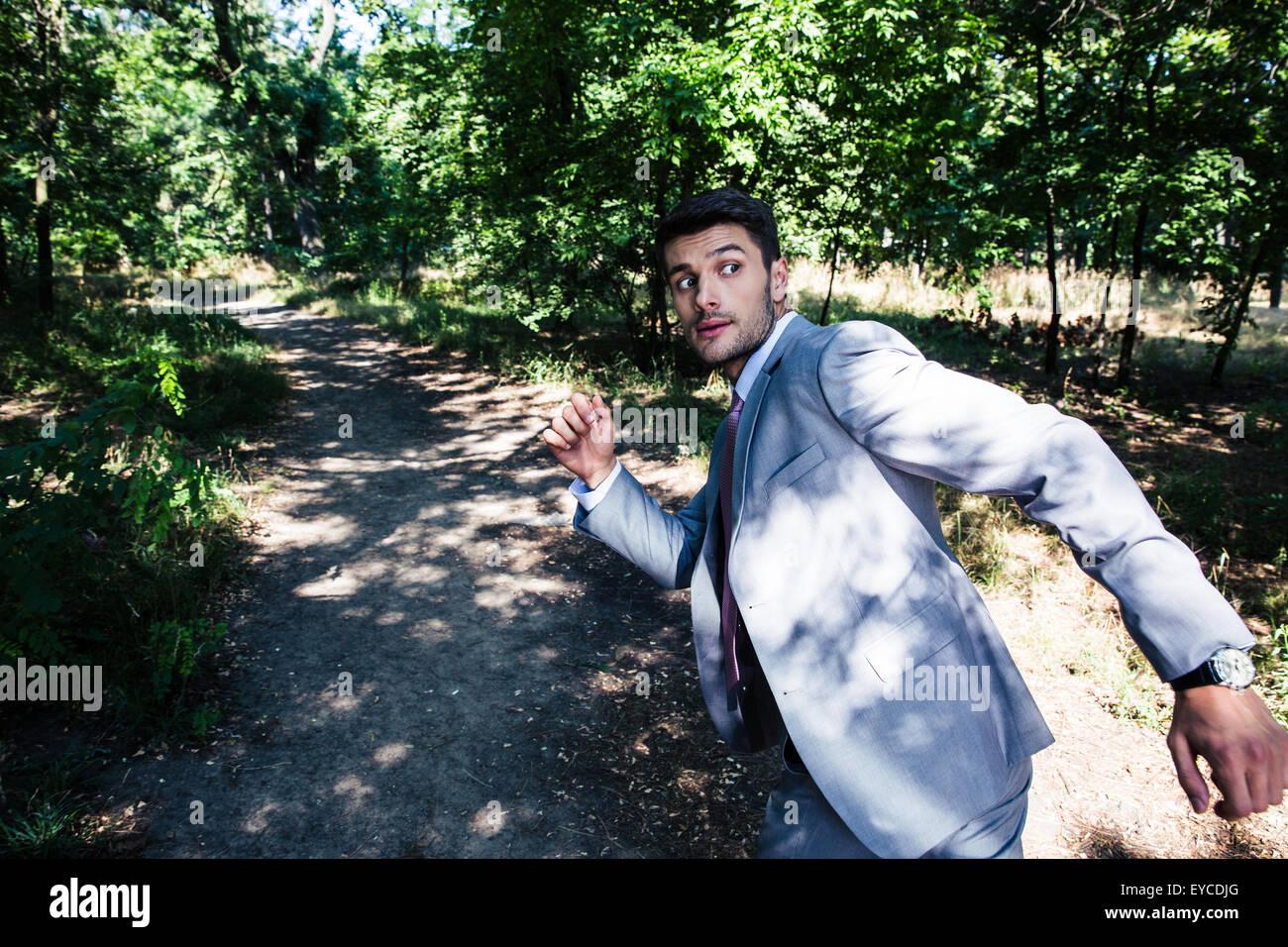 Empresario de miedo huyendo de algo al aire libre en el parque Imagen De Stock