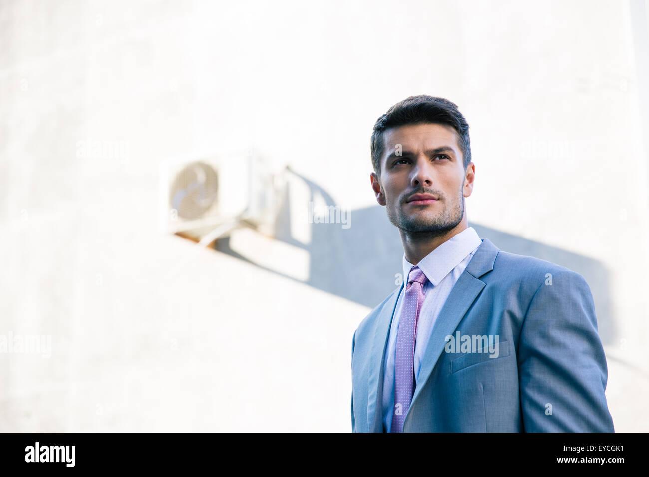 Retrato de un guapo empresario reflexivo de pie afuera Imagen De Stock