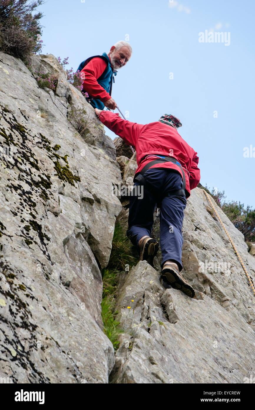 Macho inexperto escalador con cuerdas de seguridad practicando la escalada hasta una fisura en un rockface con un Imagen De Stock