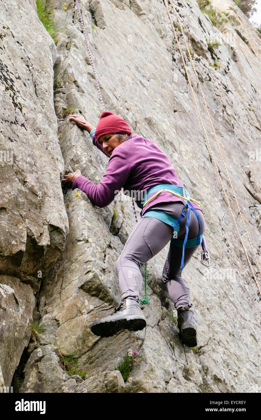 Activa Femenina senior escalador con cuerdas y arnés de seguridad subir por una grieta en un rockface. El norte Imagen De Stock