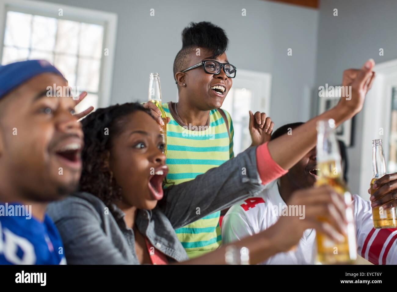 Cuatro amigos adultos aplaudiendo mientras ve la televisión desde el sofá Imagen De Stock