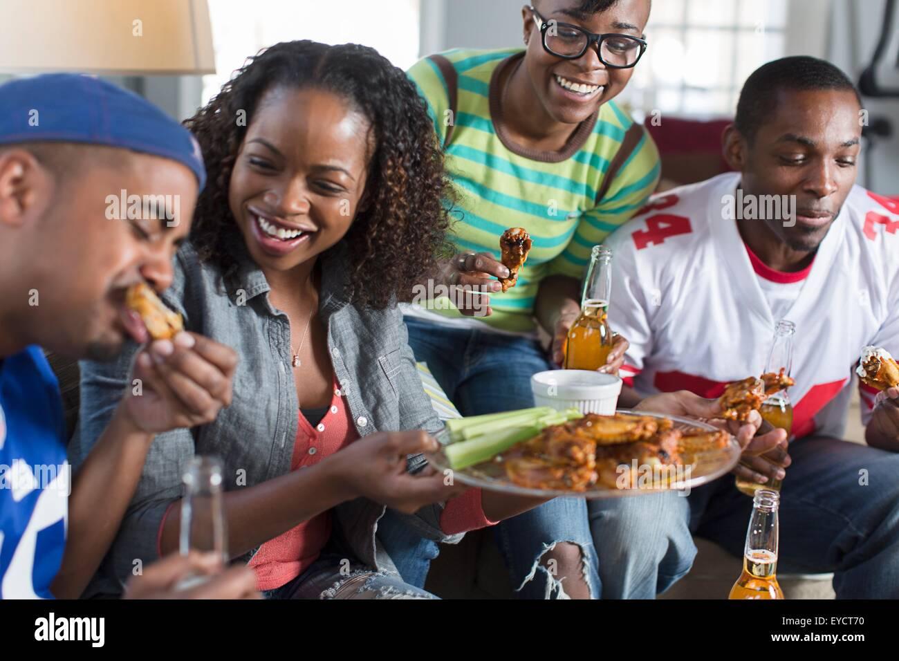 Grupo de amigos adultos comiendo comida para llevar en el sofá de la sala Imagen De Stock