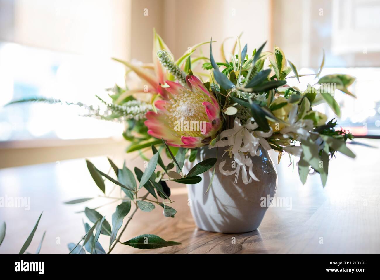 Arreglo de flores con follaje en mesa de comedor Imagen De Stock