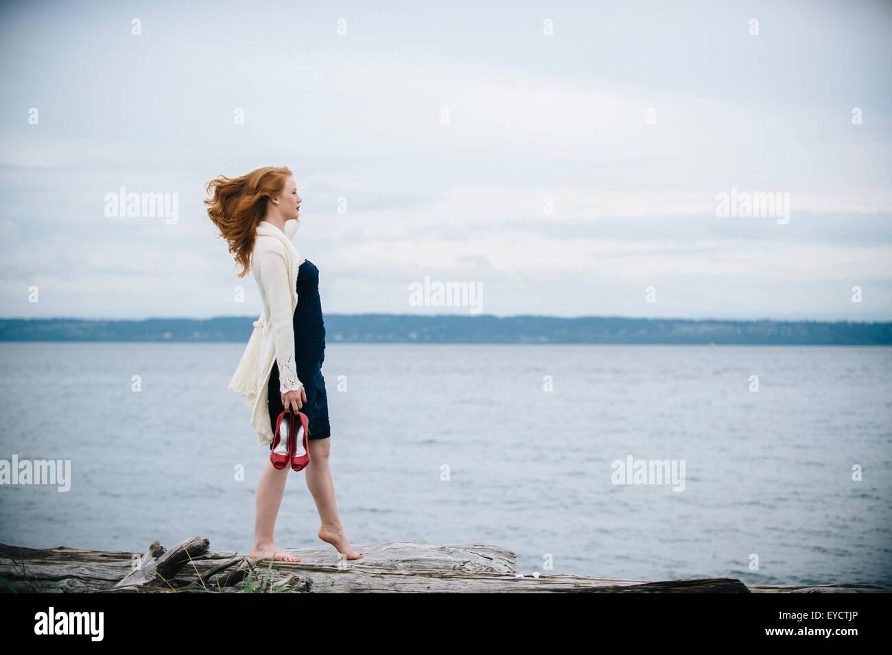 Mujer joven en la playa mirando al mar, Bainbridge Island, estado de Washington, EE.UU. Imagen De Stock