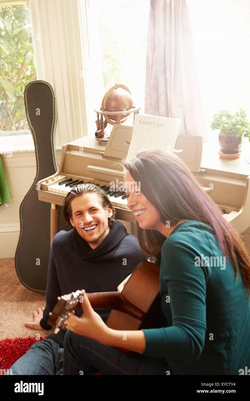 Pareja joven tocando la guitarra acústica en el salón Imagen De Stock