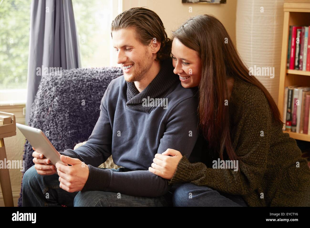 Pareja joven navegación tableta digital en el salón Imagen De Stock