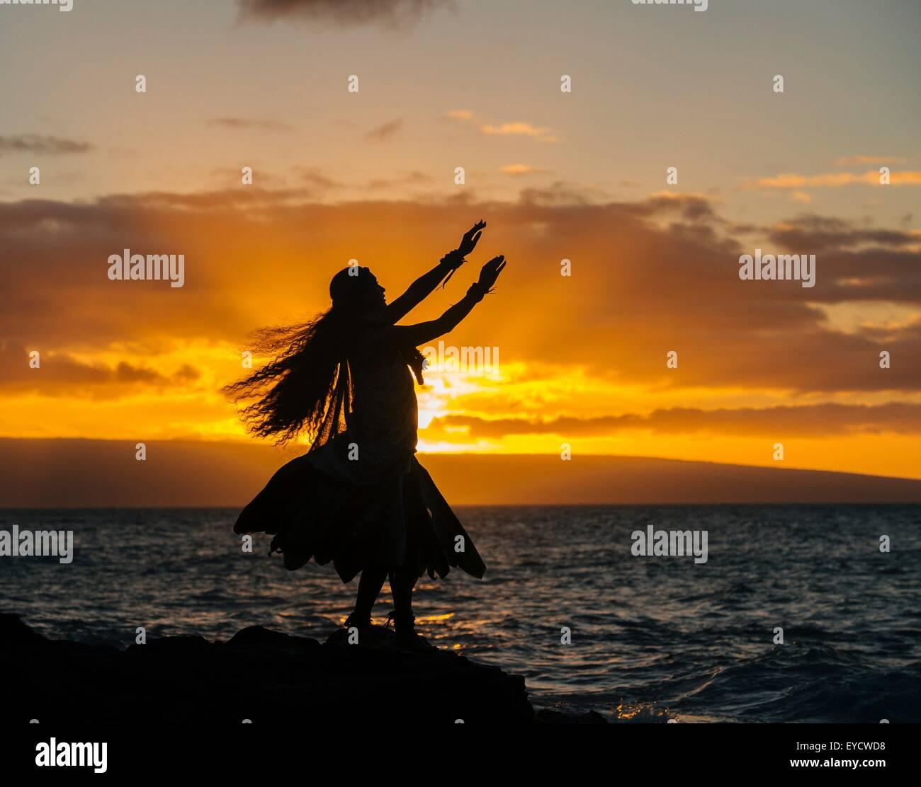 Siluetas de mujer joven con traje tradicional, hula dancing en la costa de roca al atardecer, Maui, Hawaii, EE.UU. Foto de stock