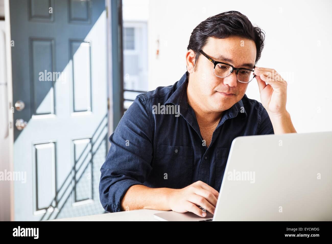 Empresario maduro para concentrarse en la laptop en la cocina Foto de stock