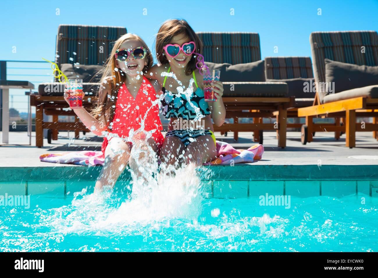 Las niñas sentadas en la piscina las salpicaduras de agua. Imagen De Stock
