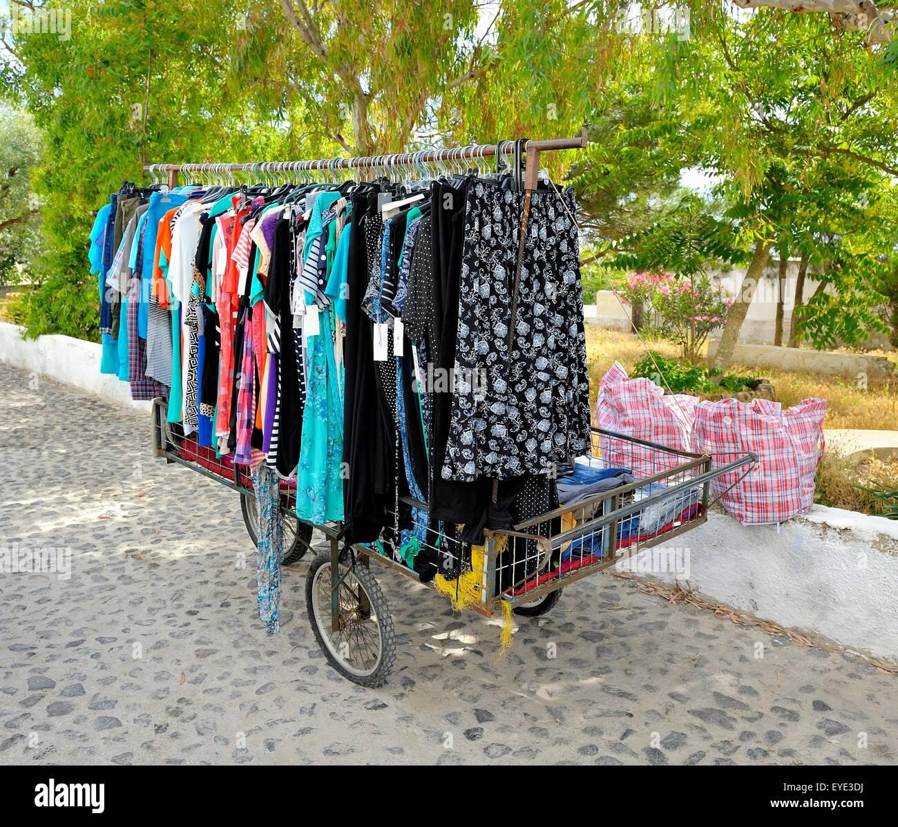 Una mujer local con un mercado móvil puesto de venta de ropa infantil. Santorini, Grecia Imagen De Stock