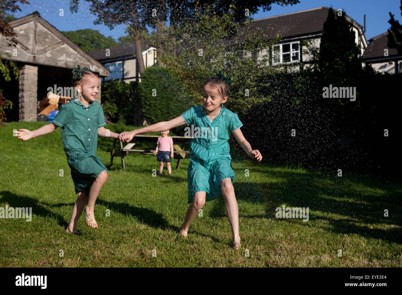 Dos niños en la escuela, vestidos que se ejecutan a través de un rociador de agua. Imagen De Stock