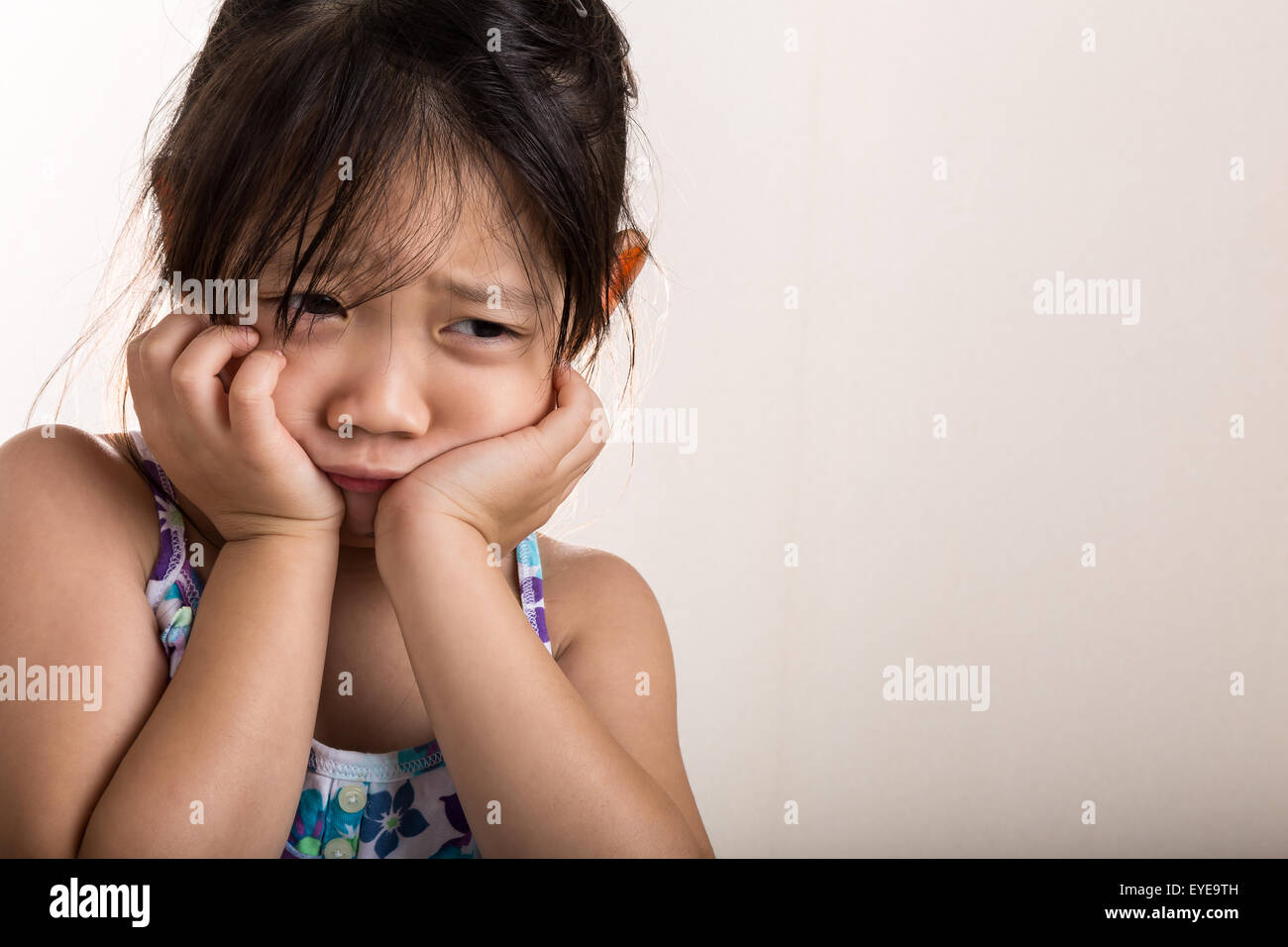 Triste niña aislado sobre fondo blanco. Foto de stock