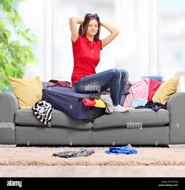 Malestar joven mujer sentada sobre su maleta en casa y tratar de colocar toda su ropa en el mismo tiro con lente Imagen De Stock