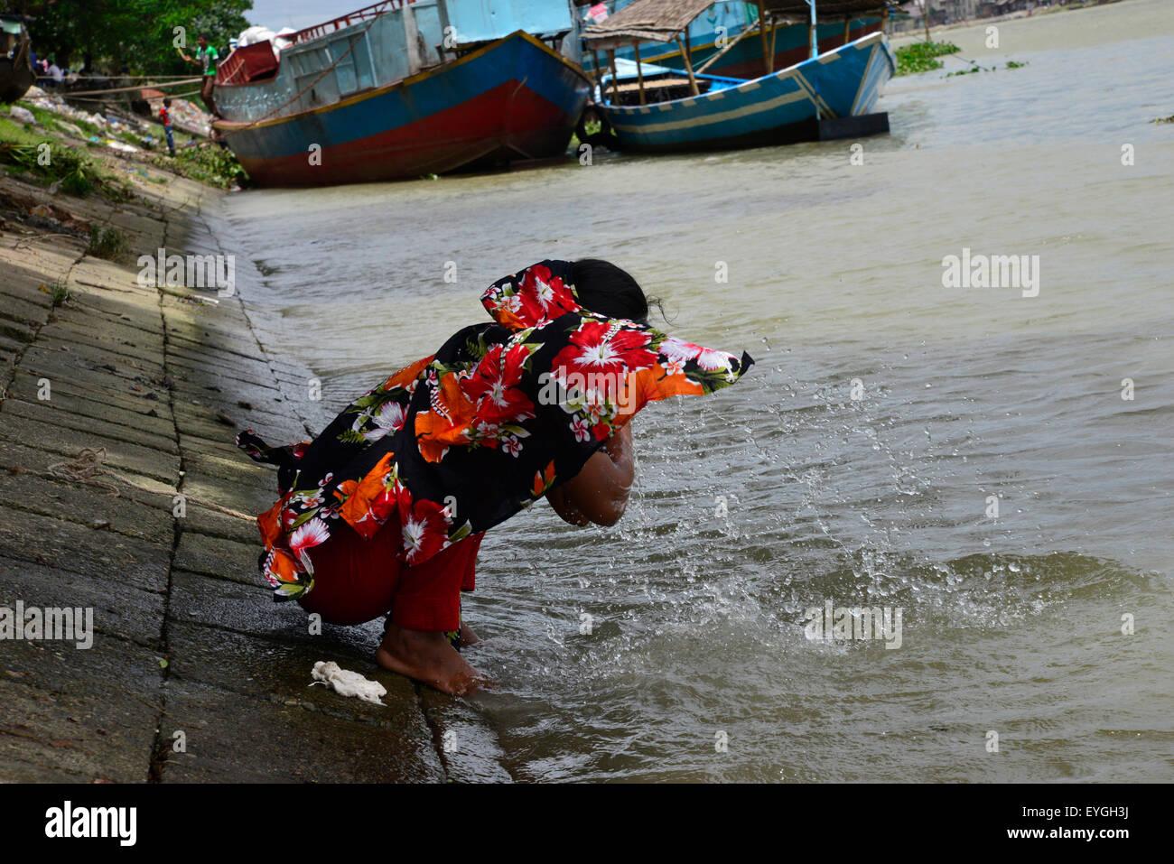 Una mujer lavándose la cara por ríos de agua en Dhaka, Bangladesh. Imagen De Stock