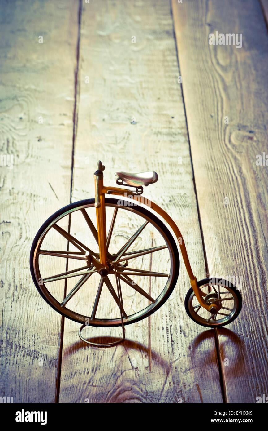 Vieja bicicleta con grande y pequeña rueda sobre una superficie de madera. Imagen De Stock