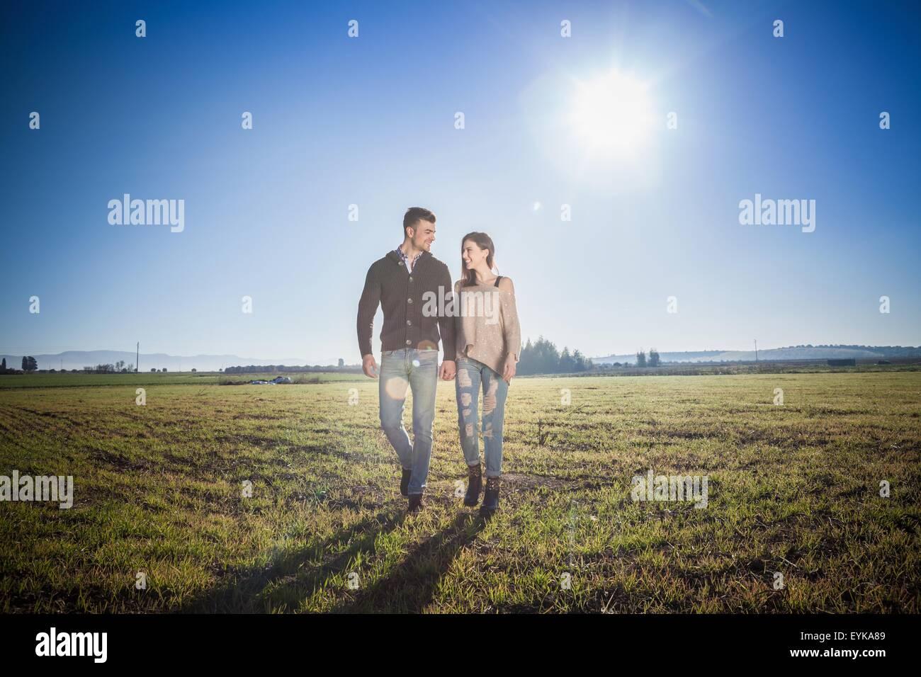 Joven pareja tomados de las manos en el campo Foto de stock