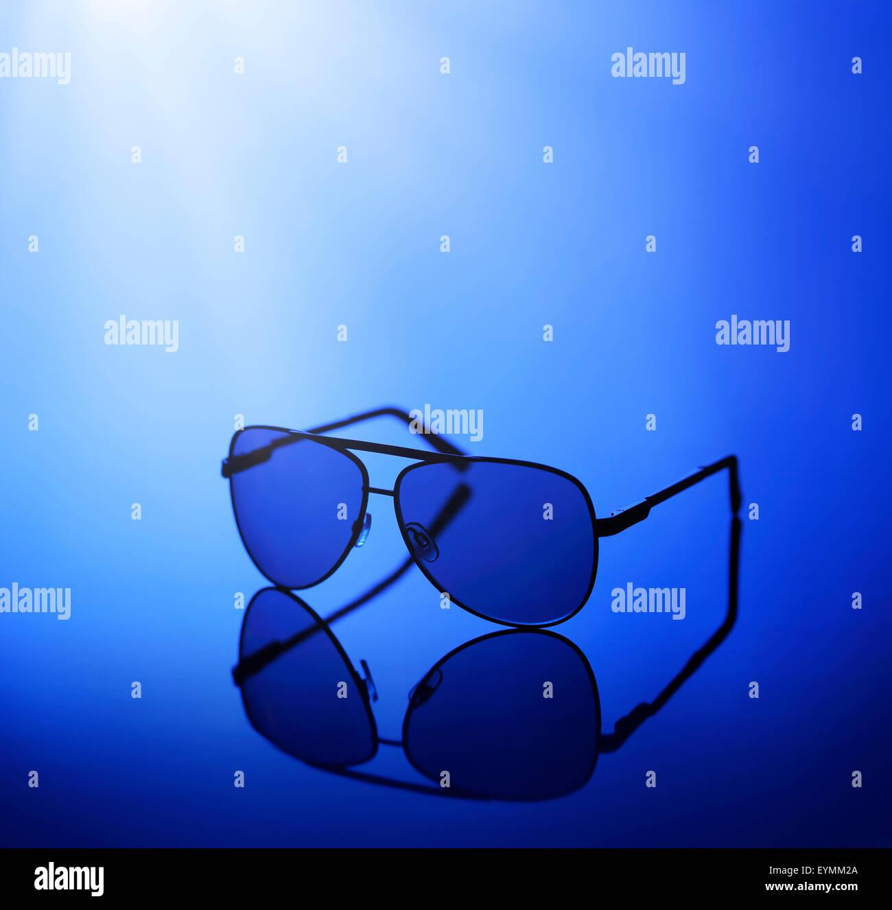 Gafas de sol en azul claro sobre un fondo reflectante. Imagen De Stock