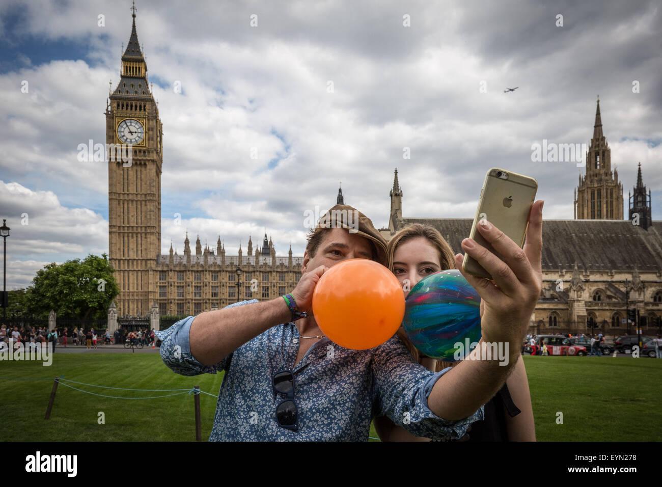 """Londres, Reino Unido. El 1 de agosto de 2015. Los activistas inhalar globos inflados con óxido nitroso, conocido comúnmente como """"gas de la Risa"""" para obtener alta durante una protesta en la Plaza del Parlamento de Westminster contra un proyecto de ley que apunta a hacer la venta de cualquier sustancia psicoactiva ilegal. Crédito: Guy Corbishley/Alamy Live News Foto de stock"""