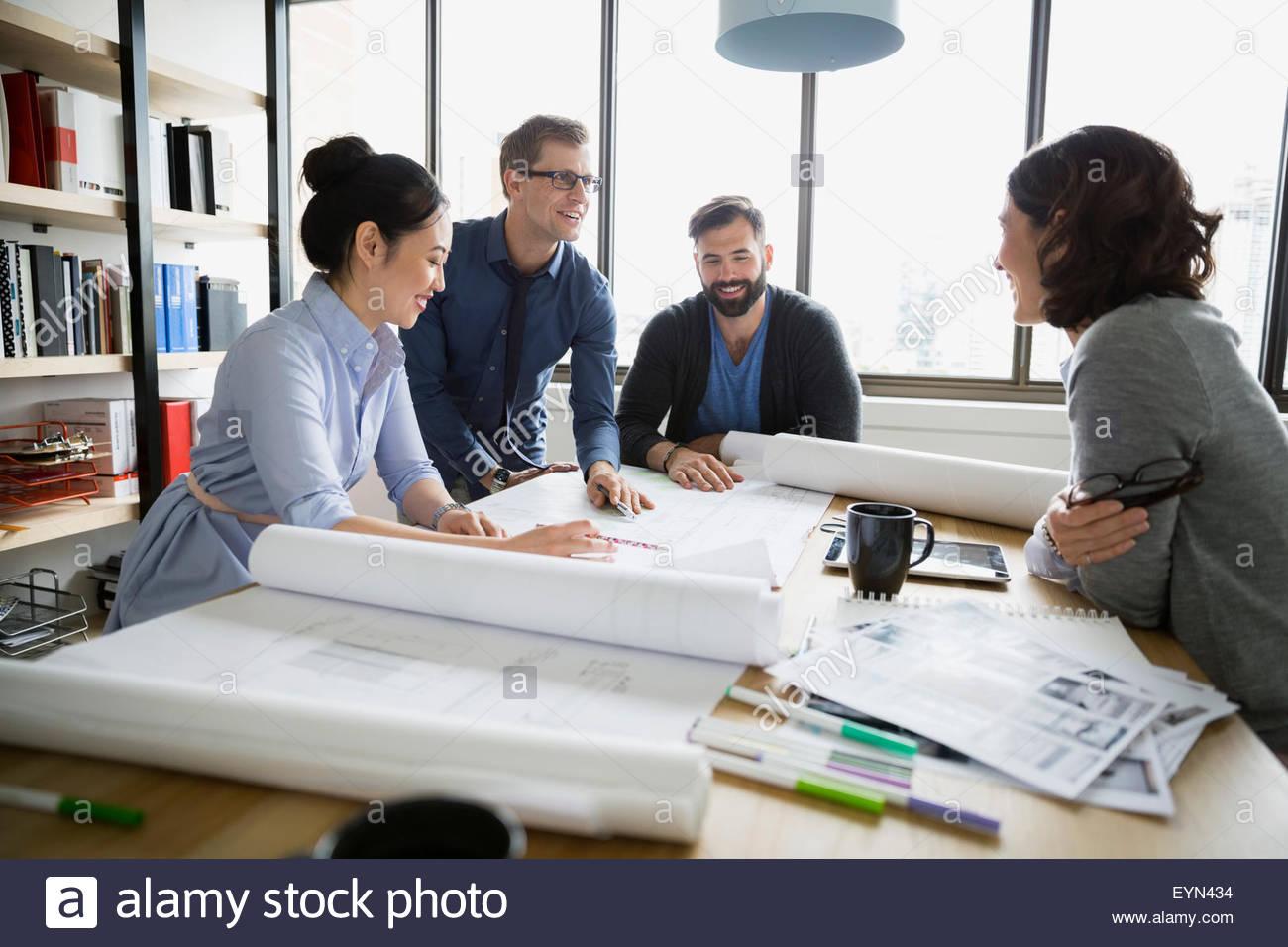 Reunión de arquitectos y revisión de planos en la oficina Imagen De Stock