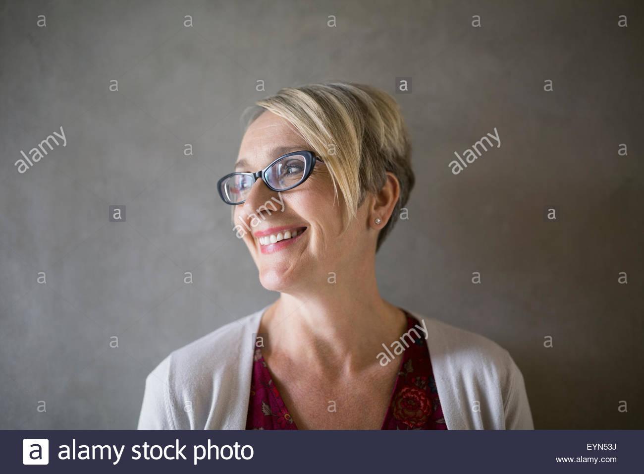 49ed31314d Retrato sonriente empresaria rubia con anteojos mirando lejos Imagen De  Stock