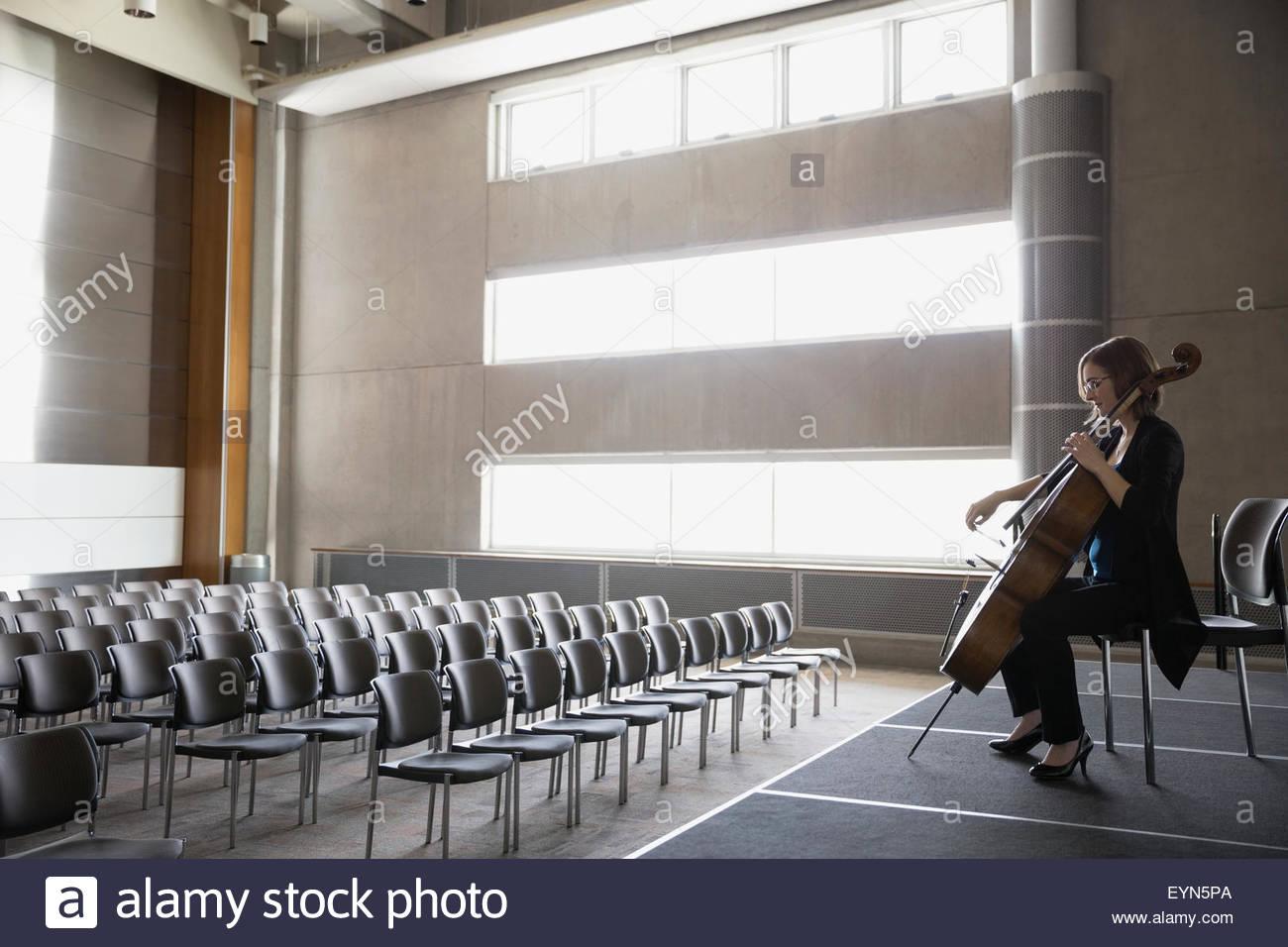 La violonchelista practicando en etapa femenina en el auditorio vacío Imagen De Stock