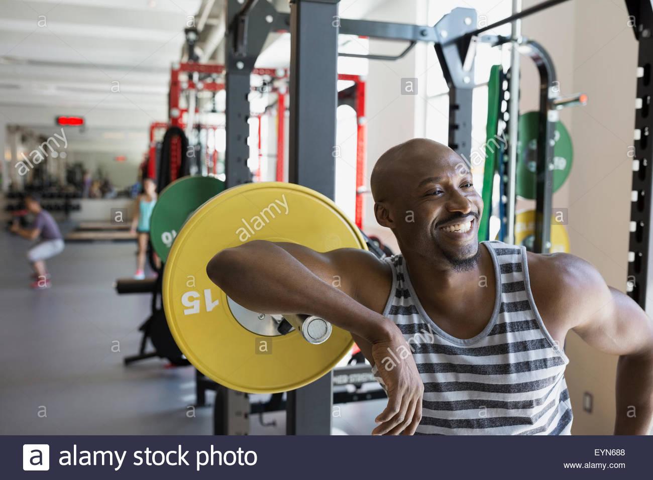 Hombre entusiasmado inclinarse sobre barbell en gimnasio Imagen De Stock