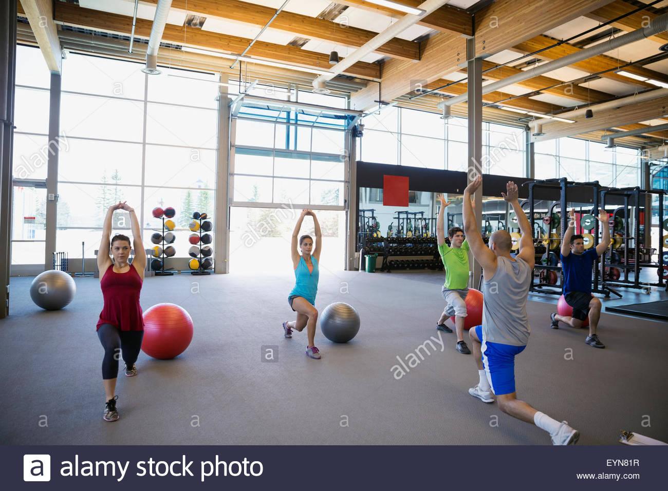Clase de ejercicios haciendo estocadas con los brazos levantados gimnasio Imagen De Stock