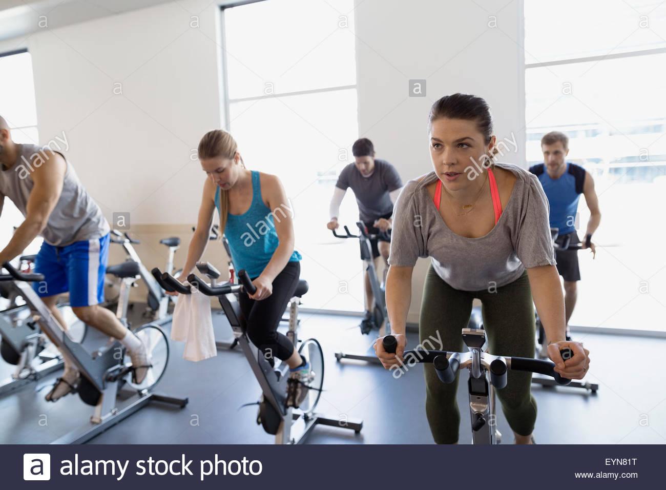 Clase de Spin en bicicletas estacionarias en un gimnasioFoto de stock