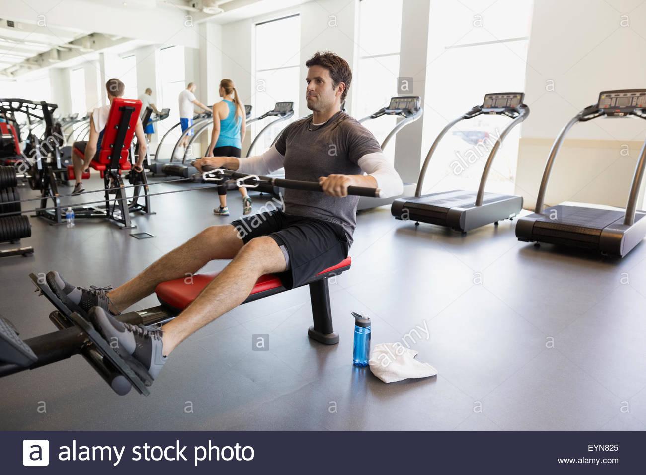 Hombre sentado haciendo fila en el gimnasio de cable Imagen De Stock