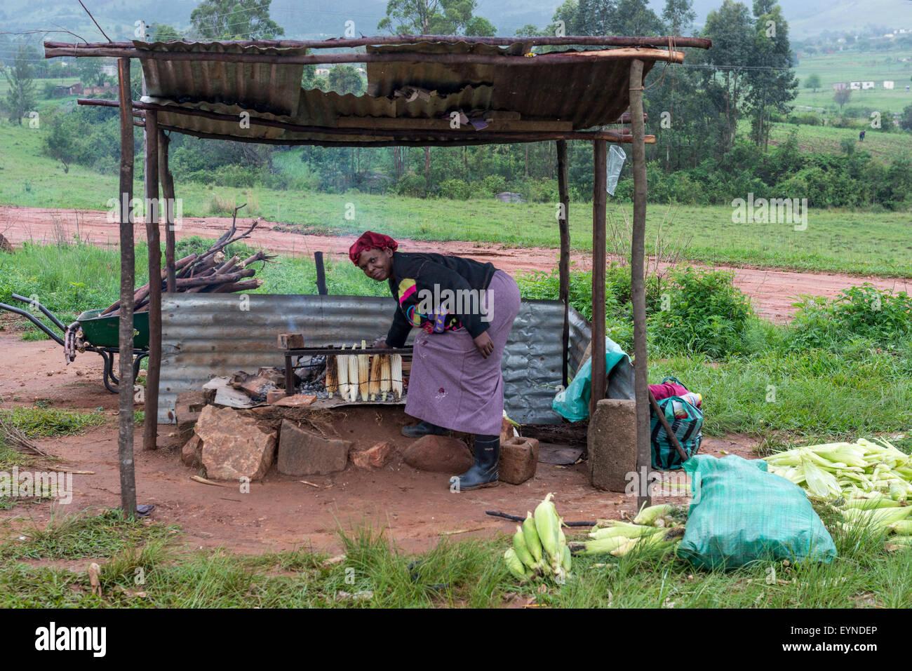 Una mujer asados de mazorcas de maíz dulce a lo largo de una carretera, Mbabane, Swazilandia Foto de stock
