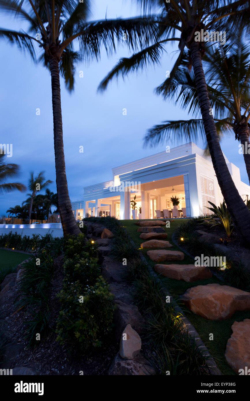 Un hermoso jardín con palmeras y piedras caminando delante de un chalet blanco Imagen De Stock